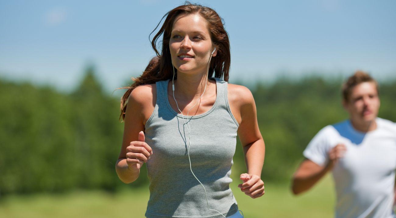 Brown hair woman with headphones jogging