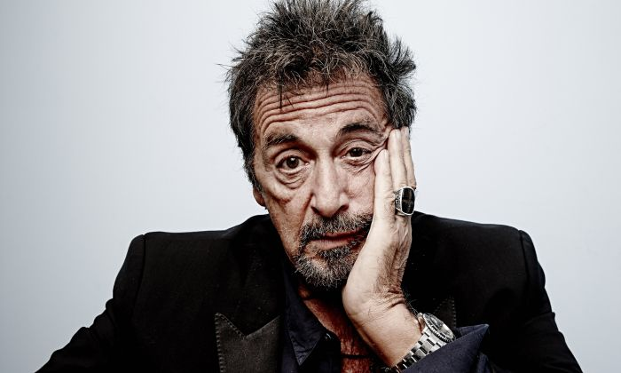 Al Pacino sits, his face leaning into one hand